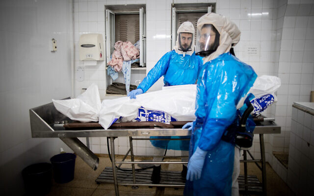 Workers from Chevra Kadisha Kehilat Yerushalayim prepare a body before a funeral at a morgue for people who died from COVID-19, at the Sanhedriya Cemetery in Jeursalem, January 25, 2021. (Yonatan Sindel/Flash90)