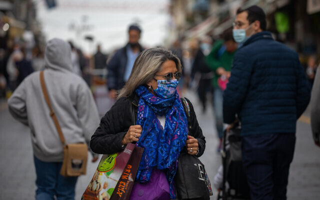 People wearing face masks walk in the Jerusalem city center on January 26, 2020, with Israel under its 3rd lockdown due to the coronavirus pandemic. (Olivier Fitoussi/Flash90)