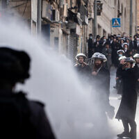 Police officers clash with ultra-Orthodox men during enforcement of the coronavirus lockdown, Jerusalem, January 26, 2021. (Yonatan Sindel/Flash90)
