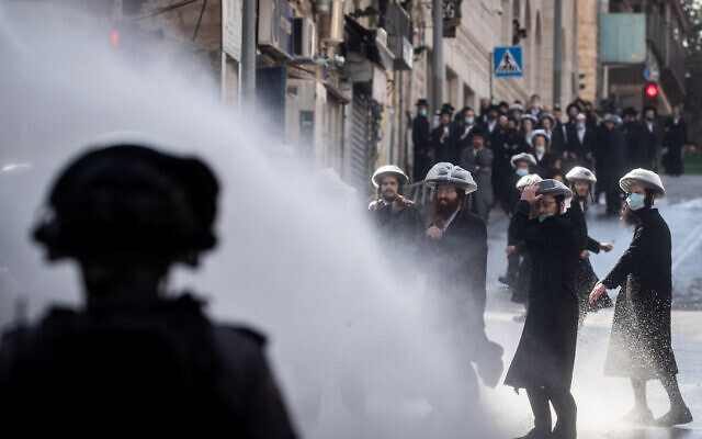 Police officers clash with ultra-Orthodox men during enforcement of the coronavirus lockdown, Jerusalem, January 26, 2021. (Yonatan Sindel/Flash90)
