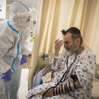 A volunteer team members wearing safety gear help a COVID-19 to lay his phylacteries in the coronavirus ward of Shaare Zedek hospital in Jerusalem on January 27, 2021, (Olivier Fitoussi/Flash90)