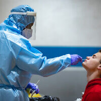 A healthcare worker takes samples at a coronavirus testing station in Jerusalem, on January 28, 2021 (Olivier Fitoussi/Flash90)