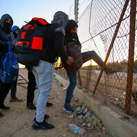 Palestinian workers from the West Bank city of Hebron carry personal belongings as they cross into Israel through a hole in  security fence near the West Bank city of Hebron, January 31, 2021. (Wisam Hashlamoun/Flash90)