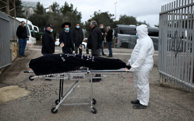 A burial services employee carries the body of Romania-born Holocaust survivor Golda Schwartz, who died at the age of 93 of complications of COVID-19 in Nof Hagalil Cemetery on January 28, 2021 (Gili Yaari / Flash90)