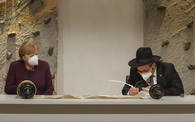 Rabbi Shaul Nekrich (R) and German Chancellor Angela Merkel (L) attend a ceremony to complete the historic Sulzbach Torah Scroll from 1792, rediscovered in 2015 and just restored, on the 76th anniversary of the liberation of Nazi Germany's Auschwitz death camp, on International Holocaust Remembrance Day, January 27, 2021 in Berlin, Germany. (Odd Andersen/Getty Images via JTA)
