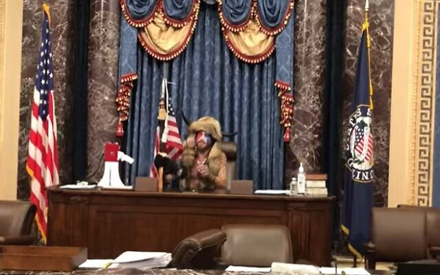 Jacob Chansley sits in Vice President Mike Pence's seat in the Senate on January 6, 2021 before leaving him a threatening note. (Screencapture/ YouTube)