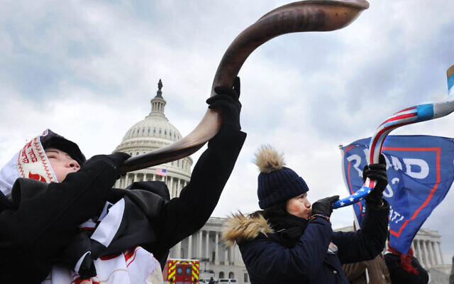 Two women, one wearing a tallit, blow the shofar amid the Capitol rioting, Jan. 6, 2021. (Lloyd Wolf via JTA)