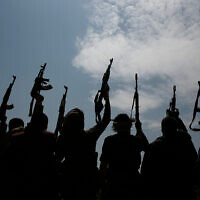 Illustrative: Tribesmen loyal to the Houthi rebels raise their weapons and chant slogans during a gathering against the agreement to establish diplomatic relations between Israel and the United Arab Emirates in Sanaa, Yemen, August 22, 2020. (AP/Hani Mohammed, File)
