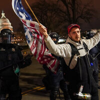 A police line moves a protestor outside of the US Capitol following violent riots there, January 6, 2021. (AP Photo/John Minchillo)