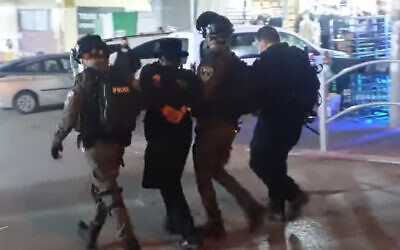 Police detain a man in the ultra-Orthodox city of Bnei Brak during clashes over virus restrictions, January 22, 2021. (Screenshot/YouTube)
