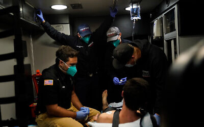 Emergency medical workers treat a patient in an ambulance during a severe COVID-19 outbreak in Placentia, California, January 8, 2021. (AP Photo/Jae C. Hong)