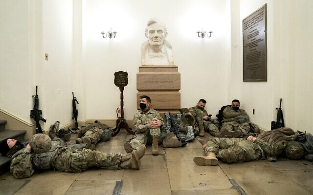 Members of the US National Guard rest in the US Capitol in Washington, January 13, 2021. (Stefani Reynolds/Getty Images/AFP)