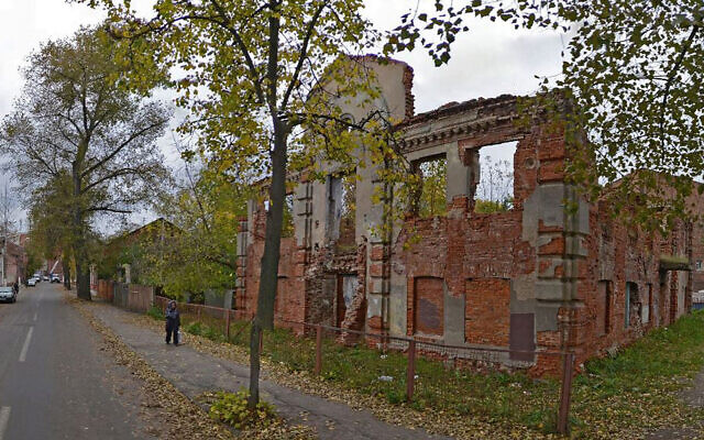 A woman walks past the ruins of the Great Lubavitch Synagogue in Vitebsk, Belarus. (Courtesy/Municipality of Vitebsk via JTA)