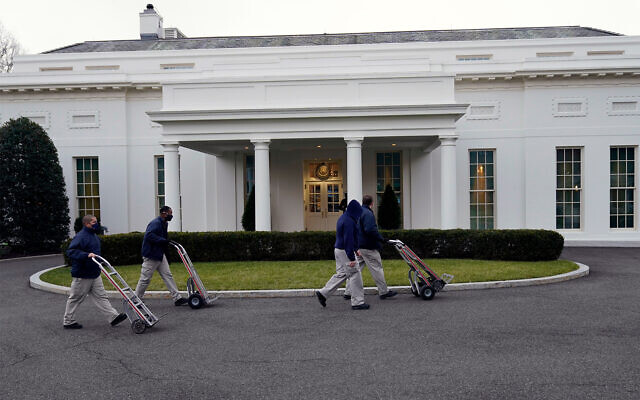 Workers walk with hand trucks past the West Wing of the White House, as offices in the White House complex are being packed up and moved out, Jan. 15, 2021. (AP Photo/Gerald Herbert)