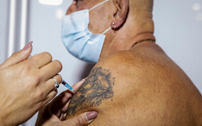 Illustrative: A COVID-19 vaccine is administered in Jerusalem, January 4, 2021. (Olivier Fitoussi/Flash90)