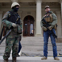 Armed civilians stand on the steps of the Michigan state capitol building after a rally in support of US President Donald Trump in Lansing, Michigan, January 6, 2021. (AP Photo/Paul Sancya)