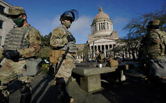Members of the Washington National Guard stand near the Legislative Building at the state Capitol in Olympia, Washington, January 10, 2021. (AP Photo/Ted S. Warren)