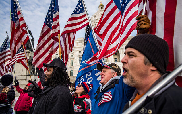 Protesters rally in support of US President Donald Trump on the steps of the Minnesota State Capitol in St. Paul, Minnesota, January 6, 2021. (Richard Tsong-Taatarii/Star Tribune via AP)