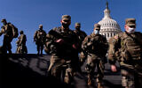 Members of the US National Guard walk past the Dome of the Capitol Building on Capitol Hill in Washington, January 14, 2021. (AP Photo/Andrew Harnik)