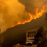 Flames crest a ridge in Salinas, Calif, Aug. 17, 2020. (AP Photo/Noah Berger)
