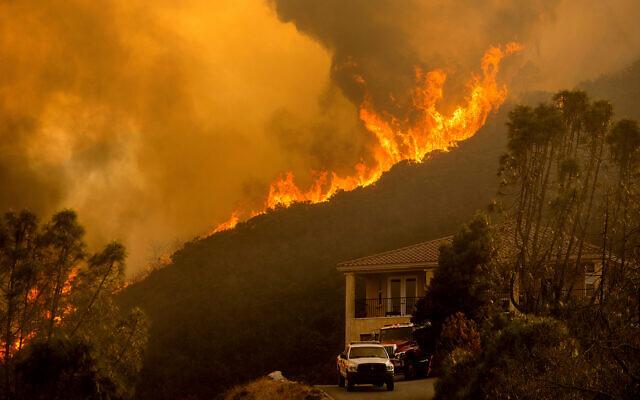 Flames crest a ridge in Salinas, Calif, Aug. 17, 2020. (AP Photo/Noah Berger)
