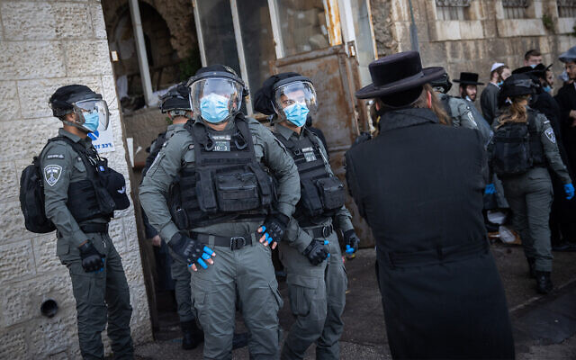 Police officers seen during clashes with ultra-Orthodox men over coronavirus lockdown restrictions, Jerusalem, January 26, 2021. (Yonatan Sindel/Flash90)