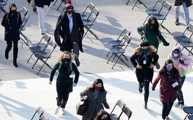 People evacuate from the West Front of the US Capitol, due to a false alarm during a rehearsal for the 59th presidential inauguration, in Washington, January 18, 2021. (AP Photo/Carolyn Kaster)