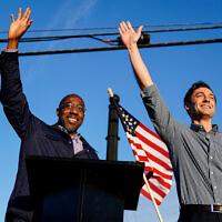 Georgia Democratic candidates for US Senate Raphael Warnock, left, and Jon Ossoff, right, gesture toward a crowd during a campaign rally in Marietta, Georgia, November 15, 2020. (AP Photo/Brynn Anderson, File)