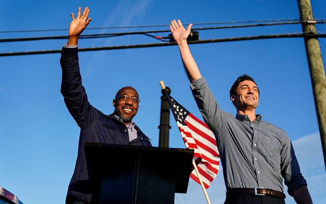Georgia Democratic candidates for US Senate Raphael Warnock, left, and Jon Ossoff, right, gesture toward a crowd during a campaign rally in Marietta, Georgia, November 15, 2020. (AP Photo/Brynn Anderson, File)
