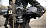 Illustrative: A member of the Boogaloo Boys extremist group stands armed with an assault rifle, gas mask and combat helmet outside of the Oregon State Capitol building in Salem, January 17, 2021. (Mathieu Lewis-Rolland/AFP)