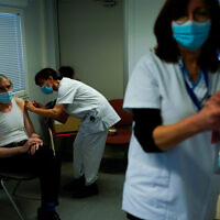 A nurse administers a Pfizer/Biontech COVID-19 vaccine to a health care worker in Liege, Belgium, January 27, 2021. (AP Photo/Francisco Seco)