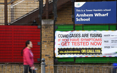 Signage gives COVID-19 safety advice on the fence a school in east London, January 3, 2021. (Daniel Leal-Olivas/AFP)