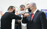 Prime Minister Benjamin Netanyahu, right, and Health Minister Yuli Edelstein, center with Muhammad Abd al-Wahhab Jabarin, the millionth Israeli to get a COVID-19 vaccine, and medical staff in Umm al-Fahm, January 1, 2021. (Haim Zach/GPO)