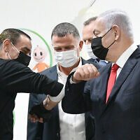 Prime Minister Benjamin Netanyahu, right, and Health Minister Yuli Edelstein, center with the millionth Israeli to get a COVID-19 vaccine and medical staff in Umm al-Fahm, January 1, 2021. (Haim Zach/GPO)