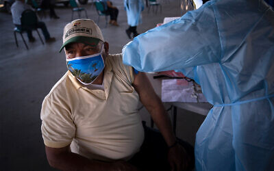 A farm worker receives the Pfizer-BioNTech COVID-19 vaccine at Tudor Ranch in Mecca, California, Jan. 21, 2021. (AP Photo/Jae C. Hong)
