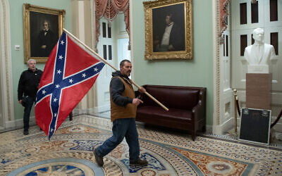 A supporter of US President Donald Trump carries a Confederate flag in the US Capitol Rotunda in Washington, DC, January 6, 2021. (Saul Loeb/AFP)