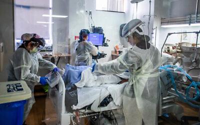 Nurses attend to a COVID-19 patient in the Intensive Care Unit Providence Cedars-Sinai Tarzana Medical Center in Tarzana, California, December 18, 2020. (Apu Gomes/AFP)
