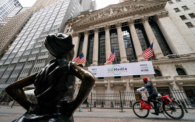 A delivery man riding a bicycle passes the New York Stock Exchange and Fearless Girl, a bronze sculpture by Kristen Visbal, in New York, January 27, 2021. (AP Photo/John Minchillo)