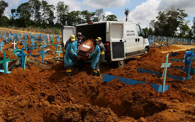 Cemetery workers carry the remains of a person who died of COVID-19 to bury in Manaus, Amazonas state, Brazil, Jan. 6, 2021. (AP Photo/Edmar Barros)