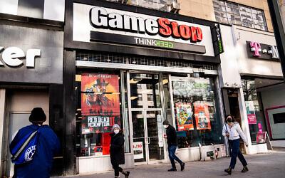 Pedestrians pass a GameStop store in New York City, January 28, 2021. (AP Photo/John Minchillo)