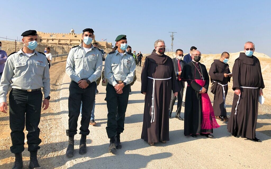 IDF officers escort Father Francesco Patton, the Custos of the Holy Land (center) and Vatican Ambassador to Israel Archbishop Leopoldo Girelli (to his right) to the St John the Baptist Chapel to the banks of the Jordan River, January 10, 2021. (Amanda Borschel-Dan/Times of Israel)