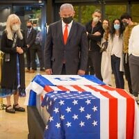 Prime Minister Benjamin Netanyahu pays his respects to the late Jewish-American billionaire Sheldon Adelson after his coffin arrived at Ben Gurion Airport, January 14, 2021. (Ami Shooman/Israel Hayom)