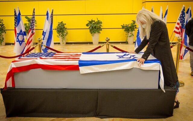 Miriam Adelson stands over the coffin of her husband, the late Jewish-American billionaire Sheldon Adelson, at Ben Gurion Airport, January 14, 2021. (Ami Shooman/Israel Hayom)
