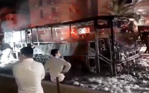 Ultra-Orthodox protesters set a bus on fire during a protest against the enforcement of the coronavirus lockdown, in the city of Bnei Brak, January 25, 2021 (Screencapture/ Twitter)