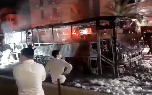 Ultra-Orthodox protesters set a bus on fire during a protest against the enforcement of the coronavirus lockdown, in the city of Bnei Brak, January 25, 2021. (Screen capture/ Twitter)