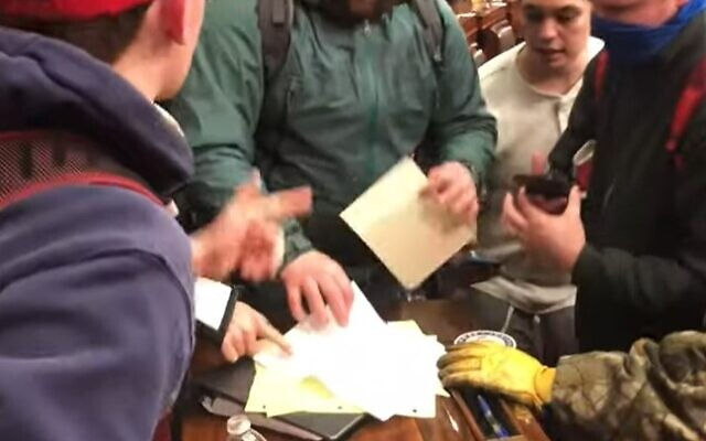 Rioters search through documents found in the Senate on January 6, 2021 (Screenshot/YouTube)
