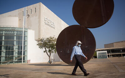 A man wears a protective face mask as he walks by the closed Habima Theater in Tel Aviv, on October 20, 2020. (Miriam Alster/ FLASH90)