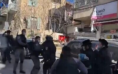 Police arrest a protester while enforcing coronavirus regulations in the Jerusalem ultra-Orthodox neighborhood of Mea Shearim, January 24, 2020 (Screen grab/Kan)