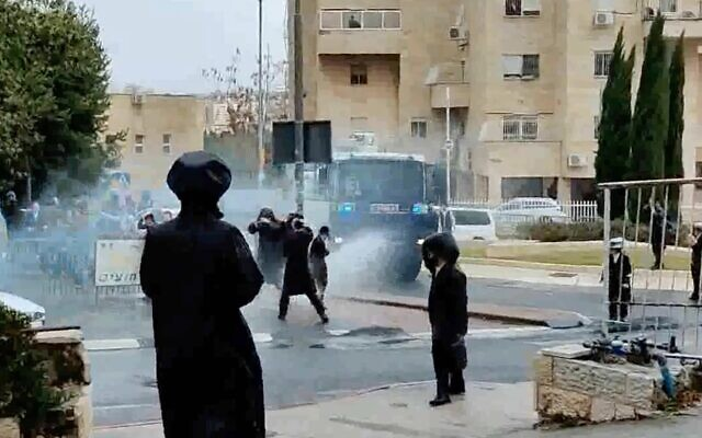 Screen capture from video as police use a water cannon to disperse protesters against enforcement of a national lockdown due to the coronavirus outbreak, in Jerusalem, January 20, 2021. (Kikar Shabbat)