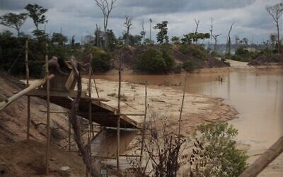 In this photo taken May 19, 2011, a miner works at an illegal mining process in Delta Uno, Madre de Dios, Peru. Mercury released by the mining is slowly poisoning people, plants, animals and fish, scientific studies show (AP Photo/Esteban Felix)